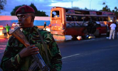 A soldier guards one of the stricken buses on Sunday
