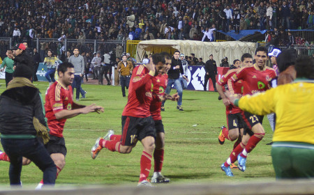 "Al-Ahly players flee Al-Masry ""ultras"" as they invade the pitch. The ensuing riot led to 72 deaths and 21 Al-Masry rioters being sentenced to death"