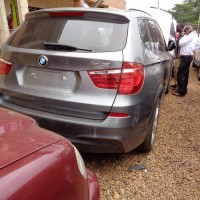Ugandan police inspect a collection of stolen BMW, Mercedes and Range Rover SUVs