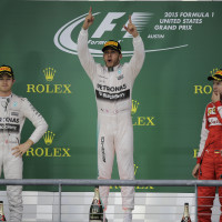Mercedes driver Lewis Hamilton, of Britain, celebrates after winning the world championship win his victory at the Formula One U.S. Grand Prix auto race at the Circuit of the Americas, Sunday, Oct. 25, 2015, in Austin, Texas. Left is teammate Mercedes driver Nico Rosberg, of Germany, and Ferrari driver Sebastian Vettel, right, of Germany,. (AP Photo/Eric Gay)